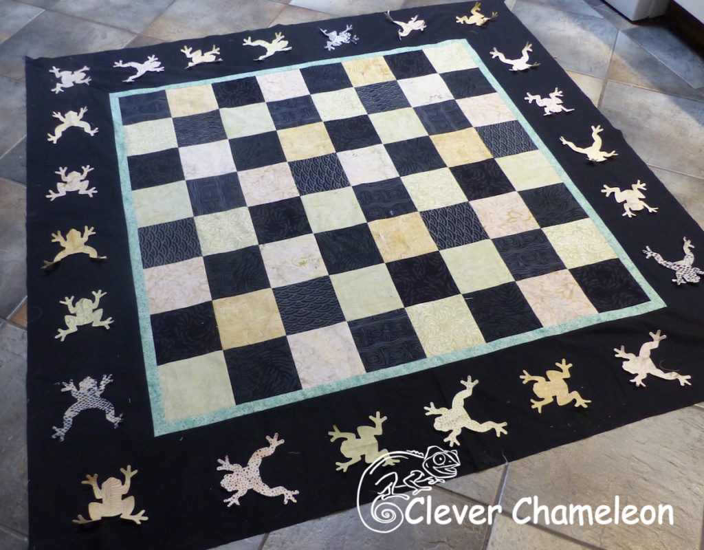 Leapfrogs around the edge of a checkerboard quilt top